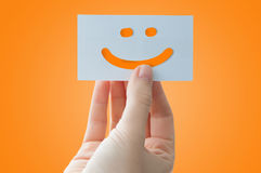 Smiley face card. Woman hand holding a smiley face card as a happy feedback announcement royalty free stock photography