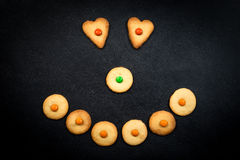 Smiley face of childish cookies on black background Royalty Free Stock Images