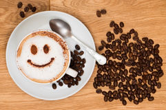 Smiley Face Coffee. Cappuccino coffee with smiley face on wooden table, overhead view royalty free stock photos