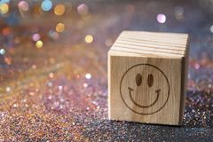 Smiley face on cube. Wood Cube with Smiley face on glitter royalty free stock image