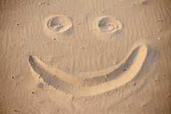 A smiley face drawing on a sand.  stock images