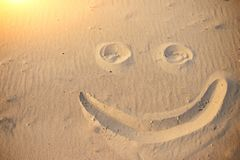A smiley face drawing on a sand.  royalty free stock photography