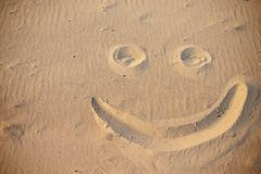 A smiley face drawing on a sand.  stock photography