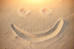 A smiley face drawing on a sand.  stock photos
