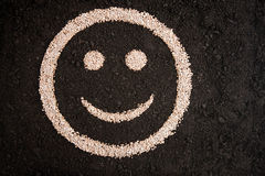 Smiley face drawing on soil. From fertilizer granules stock photos