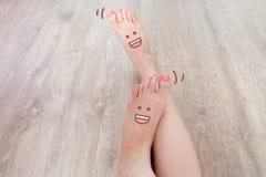 Smiley Face Drawn nos dedos do pé Feche acima da fêmea com os pés descalços no fundo de madeira do assoalho foto de stock