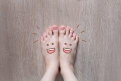 Smiley Face Drawn nos dedos do pé Feche acima da fêmea com os pés descalços no fundo de madeira do assoalho foto de stock royalty free