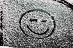 A smiley face drawn on snow-covered glass. Stock Images