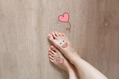 Smiley Face Drawn on Toes. Close Up Female Barefoot On Wooden Floor Background. Great for Any Use Stock Image