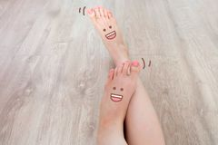 Smiley Face Drawn on Toes. Close Up Female Barefoot On Wooden Floor Background. Great for Any Use Stock Photo