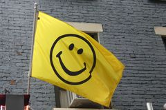 Smiley Face Flag. A yellow flag with a smiley face on it, flying in New York City royalty free stock images