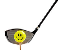 Smiley face golf ball on a tee with a driver. A yellow, smiley face golf ball on a tee with a driver on a white background Royalty Free Stock Photos