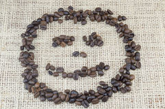 Smiley face  made entirely out of coffee grains placed on coffee Stock Image