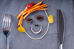 Smiley face made from vegetables, knife and fork. On a black plate royalty free stock photos