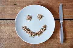 Smiley face out of breadcrumbs on white plate. Happy food message stock photos