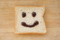 Smiley face on a piece of black bread. On wood background Royalty Free Stock Image