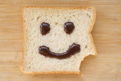 Smiley face on a piece of black bread. On wood background Royalty Free Stock Photography