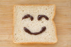 Smiley face on a piece of black bread. On wood background Stock Image