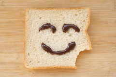 Smiley face on a piece of black bread. On wood background Stock Images