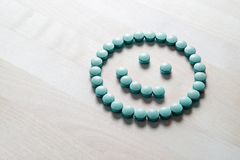 Smiley face from pills on wooden table. Happy and positive feeling from successful healing process or satisfied with health care and doctor services. Correct stock image