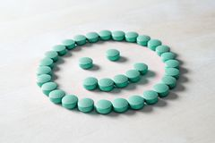 Smiley face from pills on wooden table. Happy and positive feeling from successful healing process or satisfied with health care and doctor services. Correct royalty free stock photo