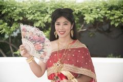 The pretty Thai lady in Middle Thai classical traditional dresses suit pose sitting hold a fan in a park. The smiley face pretty Thai lady in Middle Thai royalty free stock photos
