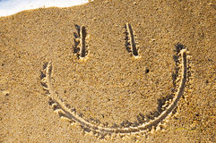 Smiley face in the sand Stock Photo