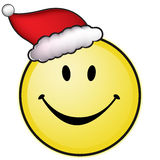 Smiley face with santa hat. Yellow happy smiley face with santa hat Royalty Free Stock Images