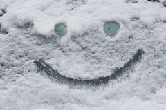 Smiley face on snow surface. Winter concept. Smiley face on snow surface. Winter outdoor concept royalty free stock photo