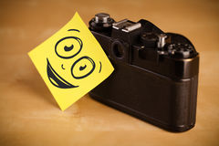 Smiley face sticked on photo camera Royalty Free Stock Images