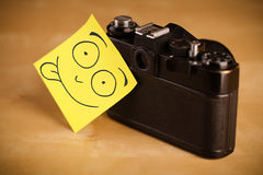 Smiley face sticked on a photo camera Royalty Free Stock Photography