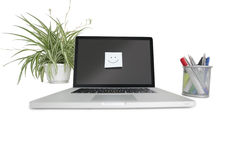 Smiley face sticky note on laptop with office supplies and pot plant Stock Photography