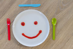 Smiley face of tomato source on white plate Royalty Free Stock Photo
