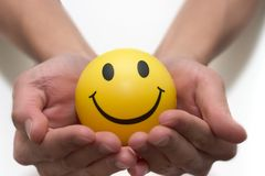Smiley face in two hands stock photo