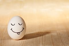 Smiley face on white egg. Smiley face with tongue on white egg Royalty Free Stock Images