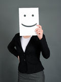 Smiley face. Woman holding a paper with smiley face royalty free stock photography