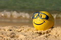 Smiley Faced Volleyball. A yellow smiley faced beach volleyball sits in the summer sand Royalty Free Stock Photography