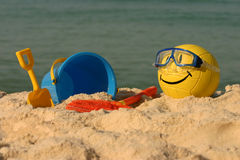 Smiley Faced Volleyball With Beach Toys. A yellow smiley faced beach volleyball sits in the summer sand with beach toys Royalty Free Stock Photos