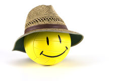 Smiley Faced Volleyball With Straw Hat. A yellow smiley faced volleyball wearing a straw hat isolated on a white background Stock Photo