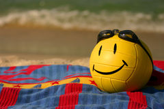 Smiley Faced Volleyball With Swim Goggles. A yellow smiley faced volleyball wearing swim goggles rests on a beach towel in the summer sand Stock Photo