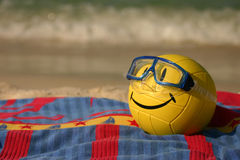 Smiley Faced Volleyball With Swim Mask. A yellow smiley faced volleyball wearing a swim mask rests on a beach towel in the summer sand Royalty Free Stock Image