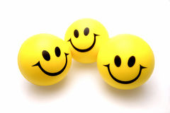 Smiley faces. Three smiley faces over white stock image