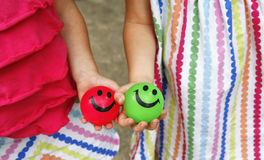 Smiley faces balls. Hands of two little girls holding colorful smiley face bouncing balls stock photo