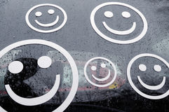 Smiley faces on car in rain Royalty Free Stock Photos