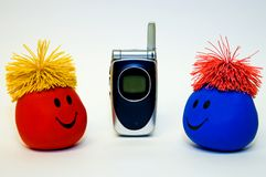 Smiley Faces and Cellphone. Two colorful smiley faces look at each other with a cellphone between them.  Possible theme: Happiness through Communication Royalty Free Stock Image