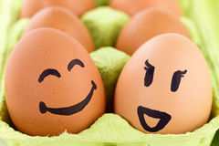 Smiley faces on eggs. Open eggbox with smiley faces isolated on white background Royalty Free Stock Images