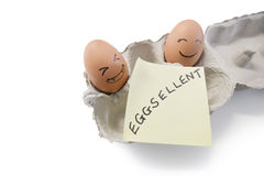 Smiley faces on eggs with 'eggsellent' written on notepaper Stock Photo