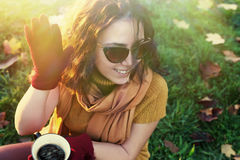 Smiley female in nature with cup of coffee in hands Royalty Free Stock Photography