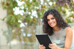Smiley flicka som rymmer en minnestavla och ser dig arkivfoton