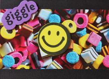 Smiley with giggle font card. A greetings card I made with modern graphic background of sweets and smiley face Royalty Free Stock Images